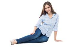Zufällige Frau, die über weißem Hintergrund sitzt Stockbilder