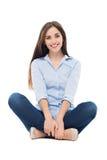 Zufällige Frau, die über weißem Hintergrund sitzt Lizenzfreies Stockbild