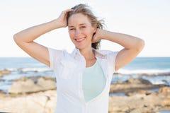 Zufällige Frau, die an der Kamera durch das Meer lächelt Lizenzfreie Stockfotos