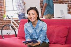 Zufällige Frau, die digitale Tablette auf Couch verwendet Stockbilder