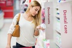 Zufällige Frau, die ein Produkt auswählt und es liest Stockbilder