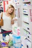 Zufällige Frau, die ein Produkt auswählt und es liest Stockbild