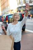 Zufällige Frau, die ein Taxi hagelt Stockbild