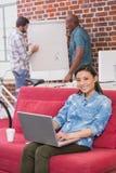 Zufällige Frau, die Laptop auf Couch verwendet Stockbild
