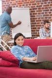 Zufällige Frau, die Laptop auf Couch verwendet Lizenzfreie Stockbilder