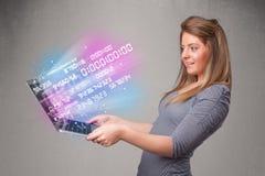Zufällige Frau, die Laptop mit explodierenden Daten und numers hält Stockbild