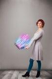 Zufällige Frau, die Laptop mit explodierenden Daten und numers hält Stockfotografie