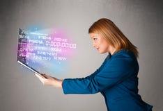 Zufällige Frau, die Laptop mit explodierenden Daten und numers hält Stockfoto