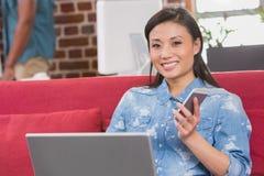 Zufällige Frau, die Laptop und Handy auf Couch verwendet Stockbilder
