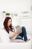 Zufällige Frau, die mit einer Tablette sich entspannt Stockbild