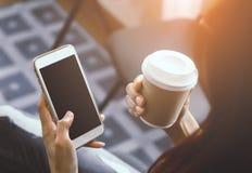 Zufällige Frau halten beweglich mit leerem Bildschirm und heißem Kaffee lizenzfreie stockbilder