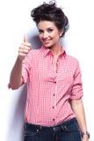 Zufällige Frau, welche die Daumen herauf okayzeichen herstellt Stockfoto
