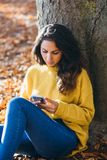 Zufällige Frauenmitteilung am intelligenten Telefon im Herbst stockfotografie