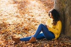 Zufällige Frauenmitteilung am intelligenten Telefon im Herbst lizenzfreie stockfotografie