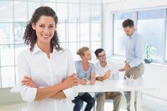 Zufällige Geschäftsfrau, die an der Kamera mit Team hinter ihr lächelt Stockbild