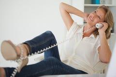 Zufällige Geschäftsfrau, die an ihrem Schreibtisch mit Füßen oben am Telefon sitzt Lizenzfreies Stockfoto