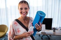 Zufällige Geschäftsfrau, die Yogamatte hält lizenzfreies stockbild