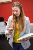 Zufällige Geschäftsfrauversenden von sms-nachrichten im Büro Stockbild