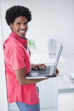 Zufällige Geschäftsmannstellung und mit Laptop Stockbilder