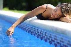 Zufällige glückliche Frau, die mit Wasser in einem Swimmingpool spielt Lizenzfreie Stockbilder