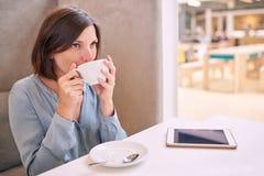 Zufällige gut gekleidete Frau, die ein Schlückchen ihres Kaffees nimmt Lizenzfreie Stockfotografie