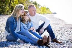 Zufällige junge Familie auf dem Strand lizenzfreie stockfotografie