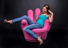 Zufällige junge Frau, die auf MP3-Player hört Stockfotografie
