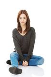 Zufällige junge Frau, die auf weißem Boden sitzt Lizenzfreies Stockbild