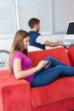 Zufällige junge Frau, die digitale Tablette auf Sofa verwendet Lizenzfreie Stockfotos