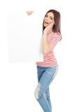 Zufällige junge Frau, die ein weißes Brett hält Stockbilder