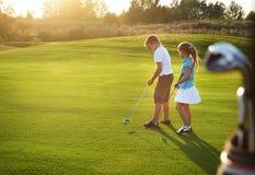 Zufällige Kinder an einem Golf fangen das Halten von Golfclubs auf Stockbild