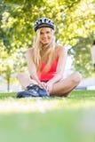 Zufällige lächelnde blonde tragende Inline-Rochen und Sturzhelmsitzen Lizenzfreies Stockbild