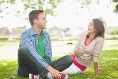 Zufällige lachende Studenten, die auf dem Gras sitzen Lizenzfreie Stockfotos