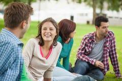 Zufällige lachende Studenten, die auf dem Grasplaudern sitzen Stockfotos