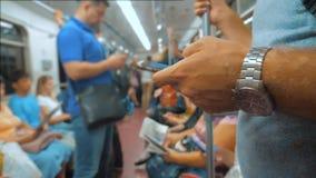 Zufällige Mannlesung vom Handy Smartphoneschirm während Blicke der Navigator, der auf Metro in der U-Bahn reist langsam stock footage