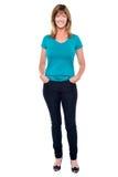 Zufällige modische Frau mit den Händen in den Jeans stecken ein Stockfotografie