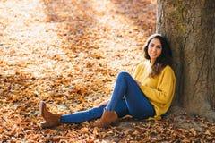 Zufällige nette Frau, die im Herbst sich entspannt lizenzfreies stockfoto