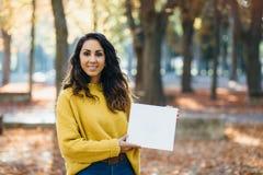 Zufällige nette Frau, die weißes Kopienraumpapier zeigt stockfoto