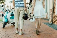 Zufällige Paare, die Sturzhelme beim zusammen draußen gehen halten Lizenzfreie Stockbilder