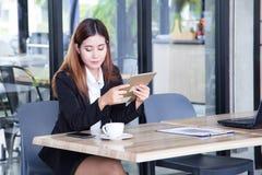 Zufällige reife Geschäftsfrau interessiert an Mobile- und Grifftablette Stockbilder