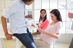 Zufällige schwangere Geschäftsfrau, die mit Kollegen arbeitet stockfoto