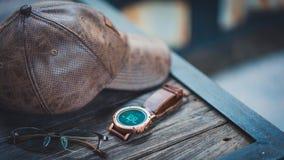 Zufällige Uhr, Hut und Gläser stockbilder
