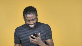 Zufälliger afrikanischer Mann im Schock während unter Verwendung Smartphones lokalisierte auf gelbem Hintergrund stock footage