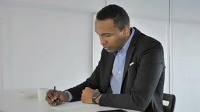 Zufälliger afroer-amerikanisch Geschäftsmann Writing bei der Arbeit, Schreibarbeit stock video