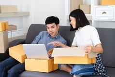 Zufälliger arbeitender Kleinbetrieb der jungen asiatischen Paare, der online sie ein Notizbuch verwendend verpackt Schauen auf ei stockbild
