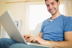 Zufälliger attraktiver Mann, der auf Couch unter Verwendung des Laptops betrachtet Kamera sitzt lizenzfreie stockbilder