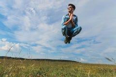 Zufälliger auf eine Rasenfläche springender und betender Mann Stockfotografie
