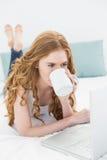 Zufälliger blonder trinkender Kaffee bei der Anwendung des Laptops im Bett Stockfotos