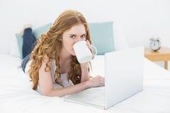 Zufälliger blonder trinkender Kaffee bei der Anwendung des Laptops im Bett Lizenzfreies Stockfoto
