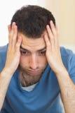 Zufälliger deprimierter Mann, der auf Couch sitzt Lizenzfreies Stockbild